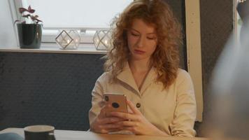 jovem branca sentada à mesa com o celular, digitando