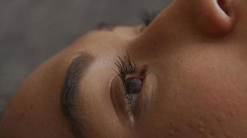 Extreme close up of eyebrows, eyes and nose of young mixed race woman, lying with back on floor