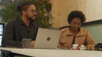svart mogen kvinna och svart man bär glasögon, sitter vid bordet på kontoret, pratar, nickar, gör en gest, kvinnan sätter koppen på bordet