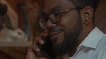 close-up de homem negro de óculos, celular na orelha, falando