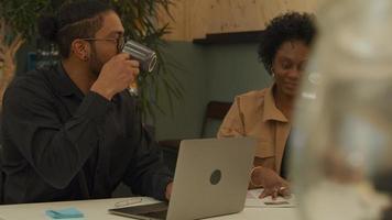 mogen svart kvinna och svart man som bär glasögon, sitter vid bordet och har en livlig konversation på kontoret