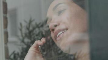 jovem mestiça parada dentro de casa atrás da janela, ligando enquanto olha pela janela video