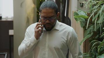 Homme noir portant des lunettes, ayant un appel téléphonique, marche et parle dans le salon video