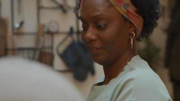 mujer negra madura habla con el hombre negro a su lado, el hombre al frente, la mujer toma la tela del mostrador video