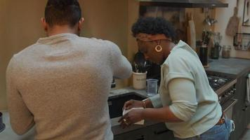 svart mogen kvinna och svart man bär glasögon som står vid köksbänken, man rör sig, kvinnan viker pappersform