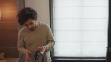 junger Mann aus dem Nahen Osten, der in der Küche steht, hält eine Kopfbedeckung des Kopfhörers gegen sein Ohr, setzt den Kopfhörer auf den Kopf und bewegt sich