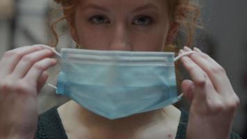 close-up van jonge blanke vrouw, ogen naar beneden, zet gezichtsmasker op met beide handen, masker aanpassen terwijl ogen in de camera kijken video