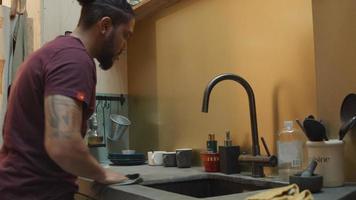 svart man i köket vid diskbänken kastar handduk och torkar köksbänken med handduk noggrant