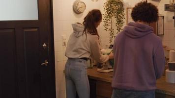 jovem mestiça limpa máquina de café na cozinha, jovem homem do Oriente Médio dobra toalha de chá e ajusta garrafas no balcão da cozinha