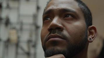 Gros plan d'un homme noir, la main sur le menton, regardant vers le haut, vers la gauche, vers la droite de manière contemplative, bouge les sourcils et se penche sur l'objectif de la caméra video