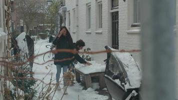Joven hombre de Oriente Medio y joven mujer de raza mixta caminando en la nieve, lanzando bolas de nieve