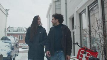 jovem homem do oriente médio e jovem mestiça andando na neve, na rua, homem passa o braço em volta da mulher, eles conversam, caminham e riem
