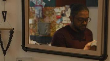 Homme noir portant des lunettes, se dirige vers le miroir dans le couloir, regarde dedans, prend son manteau, le met, met un masque facial video