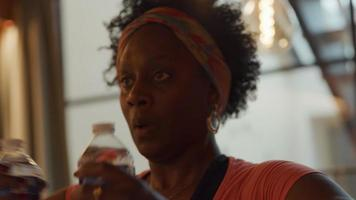 zwarte rijpe vrouw staande in de woonkamer, met twee gevulde waterflessen voor haar met gebogen armen, armen zijwaarts en rug strekt