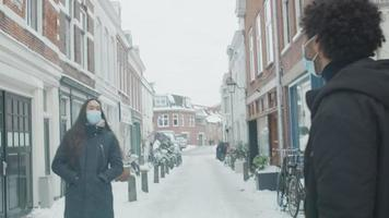Young Middle Eastern man meets young mixed race woman in street with snow with face masks on