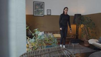 jonge vrouw van gemengd ras staat in de woonkamer, laptop vooraan aanraken, begint te springen met gebogen armen op yogamat, laptop kijken