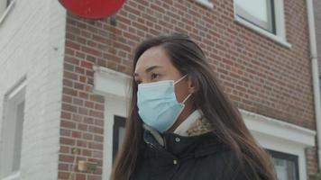 jovem mulher de raça mista com máscara facial, caminha na rua ao longo de casas