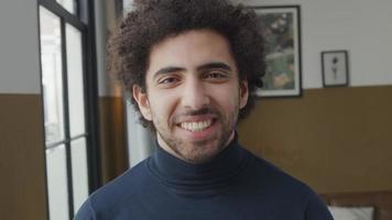 close-up de um jovem homem do Oriente Médio em pé, olhando para a câmera, rindo video