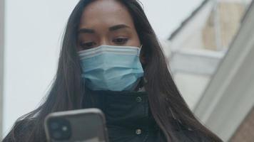 hoofd geschoten van jonge gemengd ras vrouw met gezichtsmasker, buiten staan met telefoon