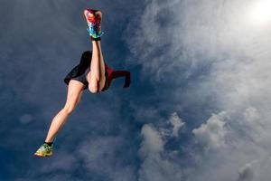 Athletic girl jumps while running in the mountains photo