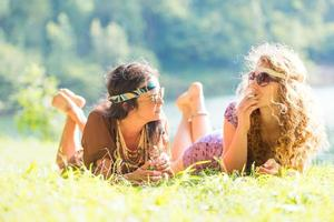 Pretty free hippie girls laying on the grass, vintage effect photo