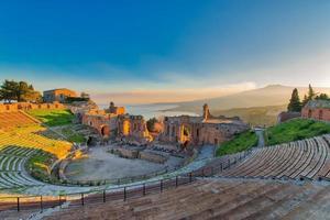 Antiguo teatro de Taormina con Etna volcán en erupción al atardecer