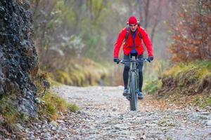 Biker with mountain bike downhill on dirt road in autumn photo