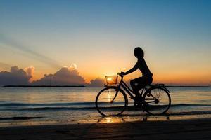 niña en bicicleta en el mar durante el amanecer foto