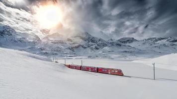 Tren de montaña suizo bernina express cruzó a través de la nieve de alta montaña foto