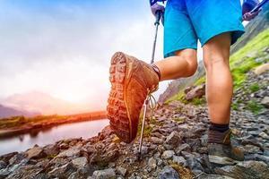 Primer plano de bota de senderismo en sendero de montaña foto