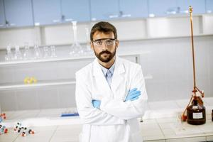 Young scientist in white lab coat standing in the biomedical lab photo