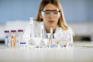 Investigadora científica o médica femenina mirando frascos con soluciones en un laboratorio foto