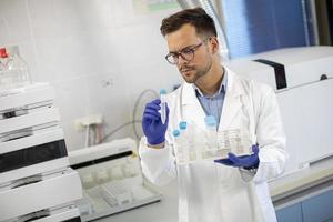 Joven investigador que trabaja con muestras químicas en laboratorio. foto