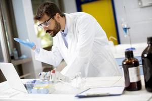Researcher in white lab coat working using laptop while sitting in the lab photo