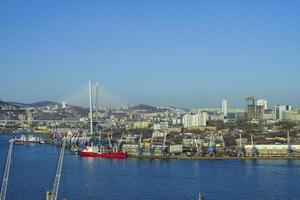 Paisaje urbano con cuerpo de agua y puerto con cielo azul claro en Vladivostok, Rusia foto