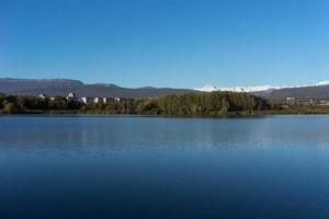 paisaje de un lago con casas y bosque con cielo azul claro foto