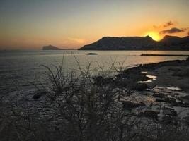 Playa mediterránea sin gente al atardecer en Calpe, Alicante foto