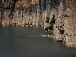 Rocas con bordes rectos durante la marea baja de una playa en la costa asturiana foto