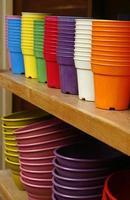 Plastic flower pots on a wooden shelf photo
