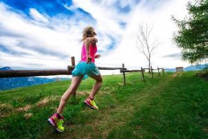 Atleta chica rubia corre un sendero de montaña en la hierba verde foto