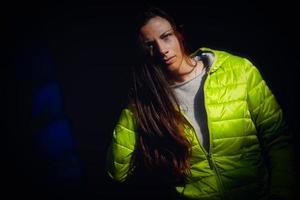 modelo de niña con chaqueta verde sobre un fondo negro foto