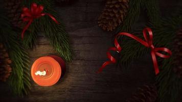 animado close-up vela de natal e galhos de árvores verdes sobre fundo de madeira