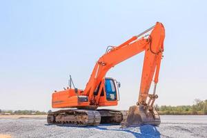 Excavator machine on a construction against blue sky background