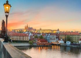 Panorama of Prague Castle, Charles bridge and St. Vitus cathedral in beautiful sunset with dramatic sky photo