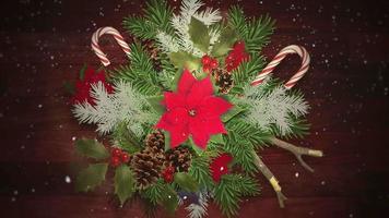 geanimeerde close-up witte sneeuwvlokken op snoep en groene kersttakken, houten achtergrond
