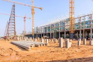 Grúas de construcción industrial y edificio en un hermoso fondo de cielo azul foto