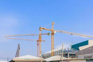 Industrial construction cranes and building in a beautiful blue sky background