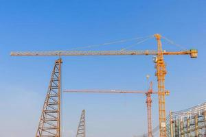 Industrial construction cranes and building in a beautiful blue sky background photo