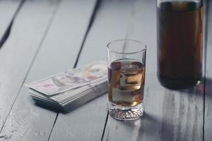 Still life with glass and bottle of alcohol and cash on wooden table photo