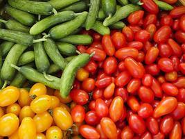 Tomates rojos y naranjas y pepino verde en el mercado foto